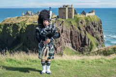 Traditional scottish bagpiper in full dress code at Dunnottar Castle. In Stonehaven Royalty Free Stock Image
