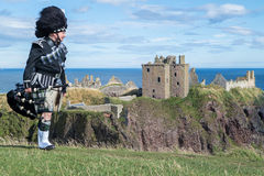 Traditional scottish bagpiper in full dress code at Dunnottar Castle Stock Photo