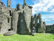 Traditional scottish bagpiper at ruins of Kilchurn castle Royalty Free Stock Images