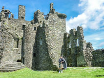 Traditional scottish bagpiper at ruins of Kilchurn castle. Traditional scottish bagpiper in Full Dress Code royalty free stock image