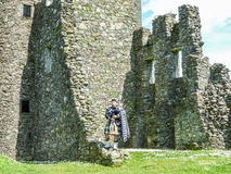 Traditional scottish bagpiper at ruins of Kilchurn castle Royalty Free Stock Image