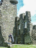 Traditional scottish bagpiper at ruins of Kilchurn castle. Traditional scottish bagpiper in Full Dress Code stock images