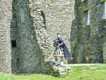 Traditional scottish bagpiper at ruins of Kilchurn castle Stock Photo