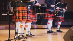 Traditional scottish band musicians singing with bagpipes and drums on the stage Royalty Free Stock Photo