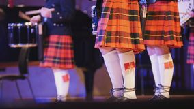 Traditional scottish band musicians singing with bagpipes on the stage during concert Stock Photos