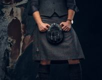 Traditional Scottish costume. Kilt and sporran. Studio photo against a dark textured wall stock images