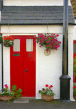 Traditional Scottish fisherman's cottage. The red door of a traditional Scottish fisherman's cottage framed with floral baskets backed by whitewashed walls Royalty Free Stock Photography