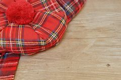 Traditional Scottish Red Tartan Bonnet and Scarf on Wood Board. Traditional Scottish Red Tartan Bonnet and Scarf Men headgear and neckwear on Grunge Timber Board Stock Photos