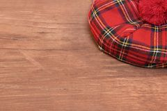 Traditional Scottish Red Tartan Bonnet on Wood Board. Traditional Scottish Red Tartan Bonnet on Grunge Brown Old Board.  Background with Free Space Stock Image