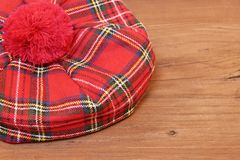 Traditional Scottish Red Tartan Bonnet on Wood Board. Traditional Scottish Red Tartan Bonnet on Grunge Brown Old Board.  Background with Free Space Royalty Free Stock Photos