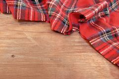 Traditional Scottish Red Tartan  Woolen Soft and Worm Scarf. On Grunge Timber Board. Background with Free Space Royalty Free Stock Photography