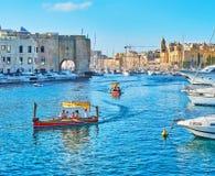 Traditional sea trips on dghajsa water taxies, Birgu, Malta. BIRGU, MALTA - JUNE 17, 2018: The measured trip to three medieval cities of Valletta Grand Harbour Royalty Free Stock Photos