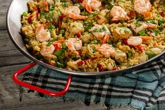 Traditional seafood paella with shrimp, fish and chicken seved in paellera. Spanish cuisine Royalty Free Stock Photography