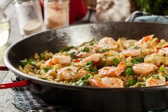 Traditional seafood paella with shrimp, fish and chicken seved in paellera. Spanish cuisine Royalty Free Stock Photo