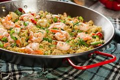 Traditional seafood paella with shrimp, fish and chicken seved in paellera. Spanish cuisine Royalty Free Stock Photos