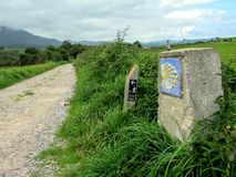 Traditional shell sign and arrow painted on the way. Direction sign for pilgrims in Saint James way, Camino de Santiago. De Compostela royalty free stock photography