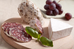 Traditional sliced salami with brie, grapes, basil Royalty Free Stock Photography