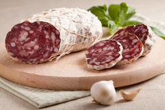 Traditional sliced salami with garlic and herbs Royalty Free Stock Images
