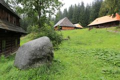 Traditional slovakian village in the Open Air Museum of ancestry. Stone on green meadow in Open Air Museum of ancestry village in Slovakia, Zuberec royalty free stock photos