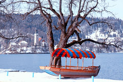 Traditional Slovenian boat and church on Lake Bled, Slovenia. Beautiful winter landscape with traditional Slovenian boat and church on Lake Bled, Slovenia Royalty Free Stock Photography