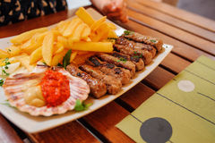 Traditional slovenian cuisine, meat kebab - chevapchichi - with french fries. Selective focus Stock Image