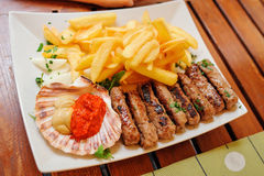 Traditional slovenian cuisine, meat kebab - chevapchichi - with french fries. Selective focus Stock Photo