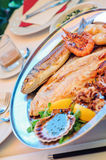 Traditional slovenian cuisine, mixed grilled fish and seafood with garlic oil Royalty Free Stock Photo