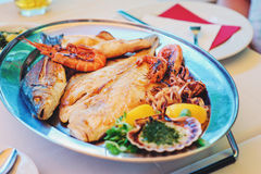 Traditional slovenian cuisine, mixed grilled fish and seafood with garlic oil. Selective focus Stock Photos