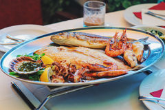 Traditional slovenian cuisine, mixed grilled fish and seafood with garlic oil. Selective focus Stock Photo