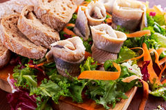 Traditional snacks salted herring with vegetables, onion, lemon, yellow lime and bread Stock Photos