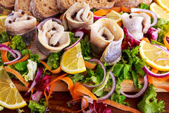 Traditional snacks salted herring with vegetables, onion, lemon, yellow lime and bread Royalty Free Stock Image
