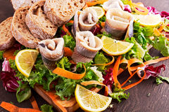 Traditional snacks salted herring with vegetables, onion, lemon, yellow lime and bread Stock Image