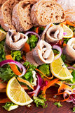 Traditional snacks salted herring with vegetables, onion, lemon, yellow lime and bread Royalty Free Stock Photos