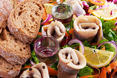 Traditional snacks salted herring with vegetables, onion, lemon, yellow lime, bread and two shots of vodka. Stock Photography
