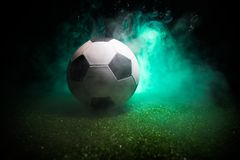 Traditional soccer ball on soccer field. Close up view of soccer ball (football) on green grass with dark toned foggy background. Selective focus stock photography
