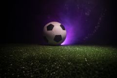Traditional soccer ball on soccer field. Close up view of soccer ball (football) on green grass with dark toned foggy background. Selective focus royalty free stock photos