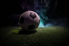 Traditional soccer ball on soccer field. Close up view of soccer ball (football) on green grass with dark toned foggy background. Selective focus royalty free stock photo