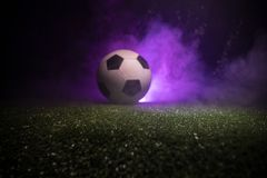 Traditional soccer ball on soccer field. Close up view of soccer ball (football) on green grass with dark toned foggy background. Selective focus stock image