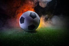 Traditional soccer ball on soccer field. Close up view of soccer ball (football) on green grass with dark toned foggy background. Selective focus royalty free stock photography
