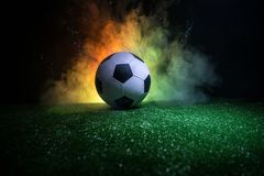 Traditional soccer ball on soccer field. Close up view of soccer ball (football) on green grass with dark toned foggy background. Selective focus stock photos