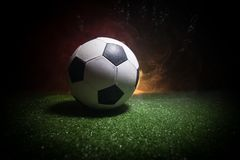 Traditional soccer ball on soccer field. Close up view of soccer ball (football) on green grass with dark toned foggy background. Selective focus stock images