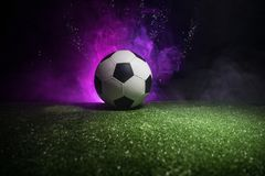 Traditional soccer ball on soccer field. Close up view of soccer ball (football) on green grass with dark toned foggy background. Selective focus royalty free stock image