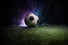 Traditional soccer ball on soccer field. Close up view of soccer ball (football) on green grass with dark toned foggy background. royalty free stock photography