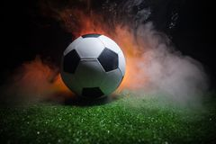 Traditional soccer ball on soccer field. Close up view of soccer ball (football) on green grass with dark toned foggy background. Selective focus royalty free stock images
