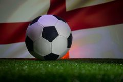Traditional soccer ball on soccer field. Close up view of soccer ball (football) on green grass with dark toned foggy background. stock images