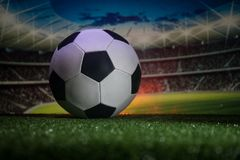 Traditional soccer ball on soccer field. Close up view of soccer ball (football) on green grass with dark toned foggy background. Stock Photo