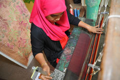Traditional Songket making. Songket is a magnificent piece of traditional Malay fabric handwoven in silk or cotton threads, using colourful metallic threads to Stock Image
