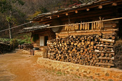 Traditional South Korean house. A traditional South Korean house with a wood pile and maize drying on a rack Royalty Free Stock Photo