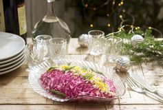Traditional Soviet festive salad of herring and vegetables, served with vodka in a New Year`s decoration. Rustic style stock photography