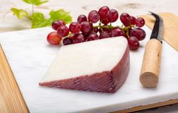 Traditional Spanish cheese, Murcian wine cheese from goat milk w. Traditional Spanish cheese, one piece of Murcian wine cheese from goat milk with rind washed in stock image